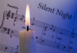A lit candle in front of the sheet music for Silent Night