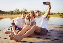 A family by the water taking a selfie on holiday