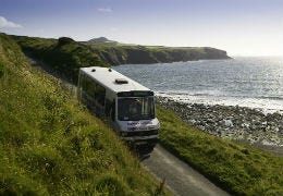 Local bus driving past the sea at Newgale