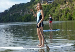 A girl stand up paddle boarding on calm water
