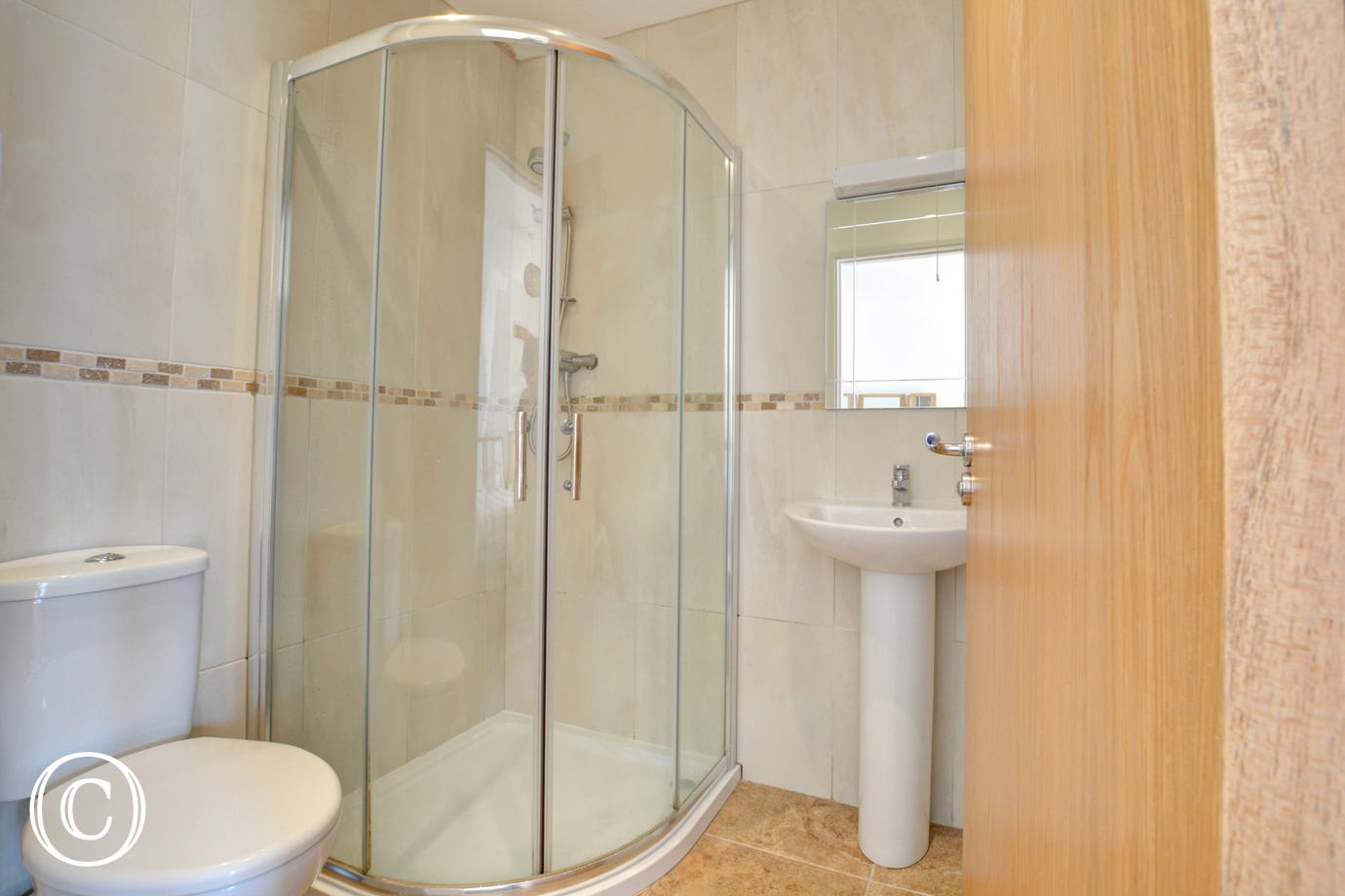 An en-suite shower room with toilet and wash basin leading from the master double.