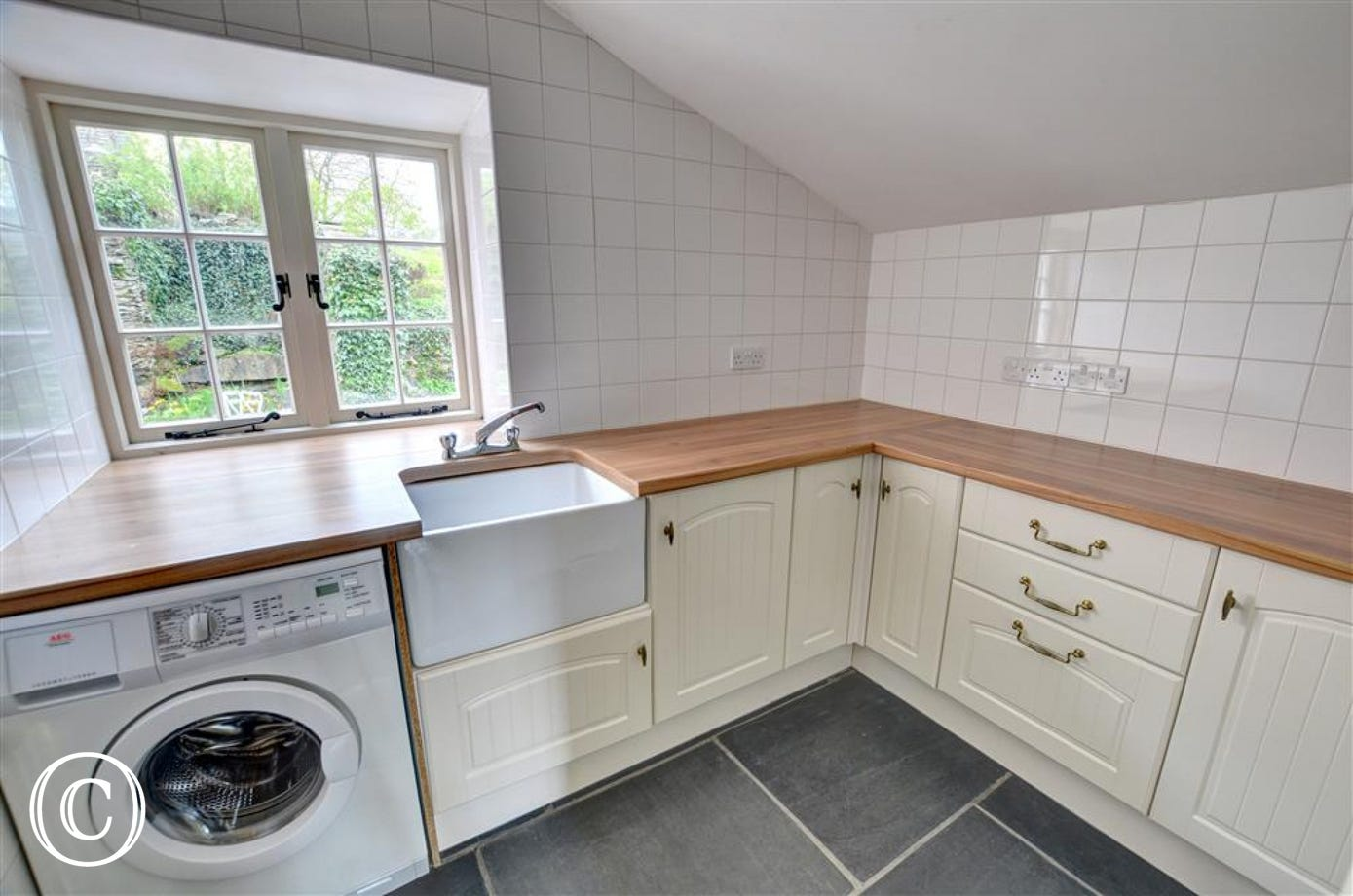 The utility room has cream fitted units