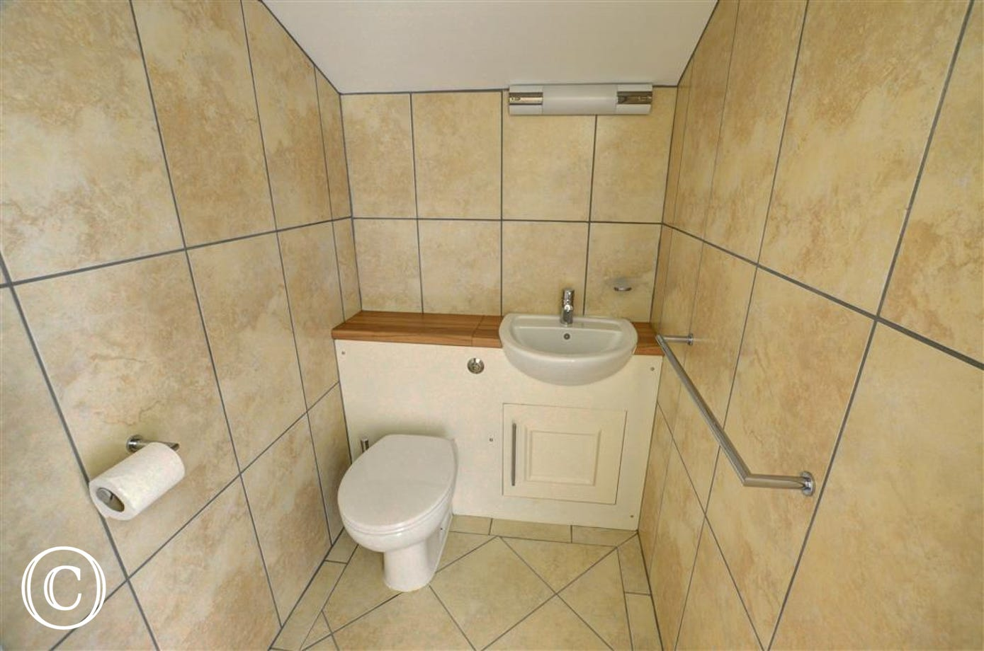 There is a second WC in a smart fully tiled cloakroom