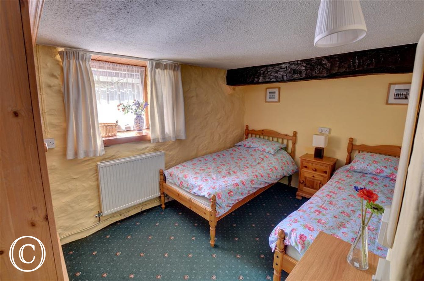 The ground floor twin bedroom is furnished in pine and has attractive linens