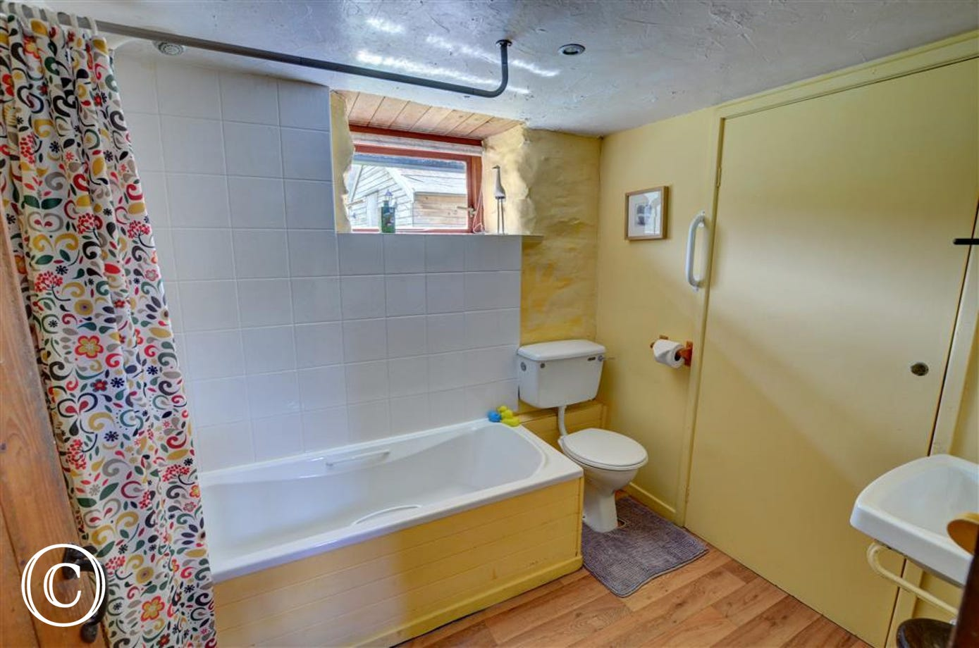 The brightly painted ground floor bathroom has a shower over the bath