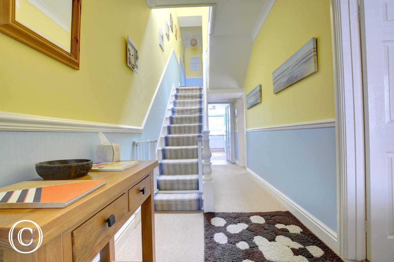 Spacious hallway leading up to bedrooms.