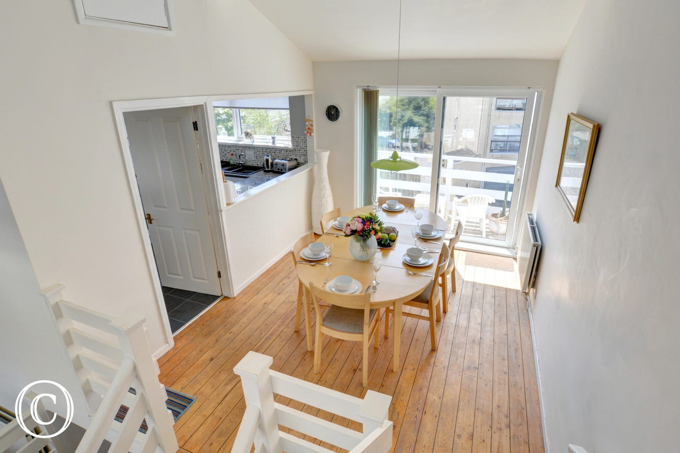 Stairs leading down from the top mezzanine area to the dining area and kitchen at this self catering holiday property.