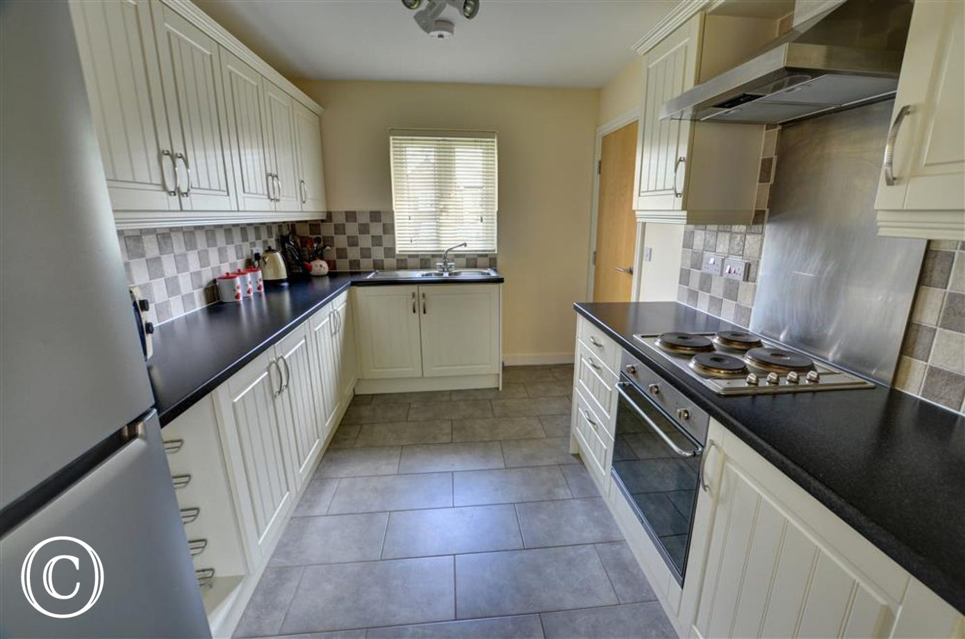 The smart fitted kitchen has light units and a tiled floor
