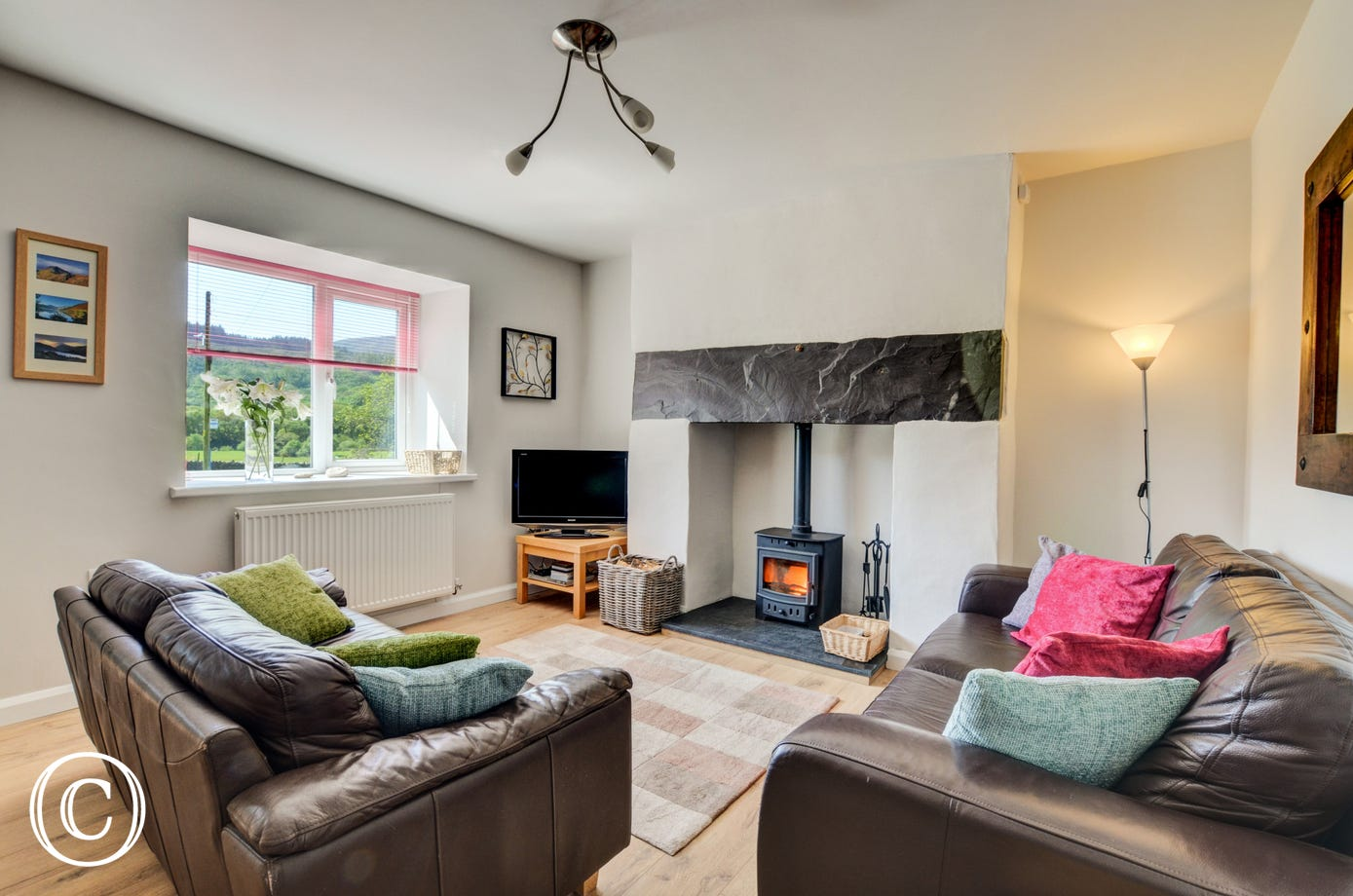 Wonderful wooden flooring in the living room complements the modern furnishings and woodburner