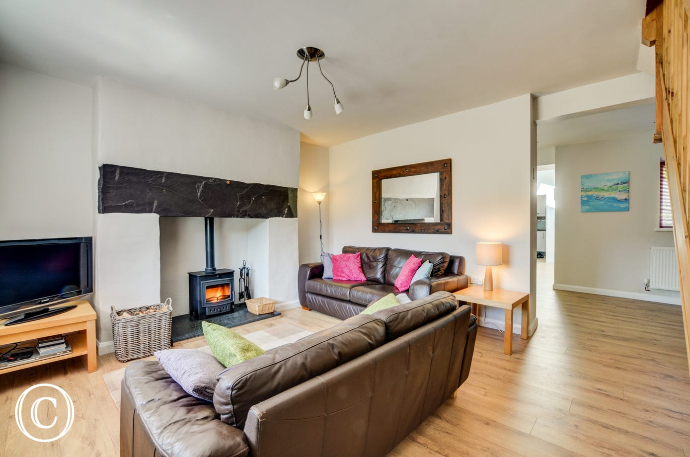 Relax on the modern leather sofas and enjoy a roaring fire from the woodburner