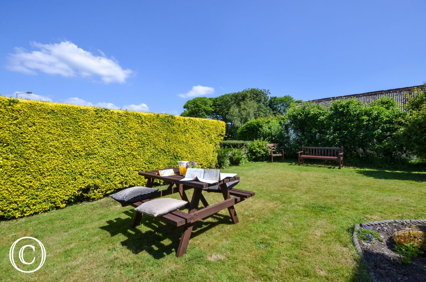 Sheltered by hedges, enjoy outdoor eating in this great garden