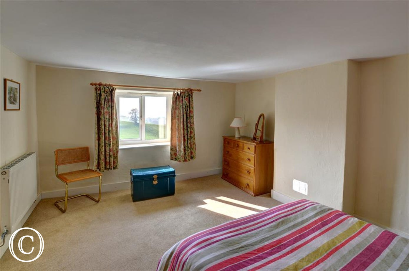 The spacious double bedroom has a lovely view