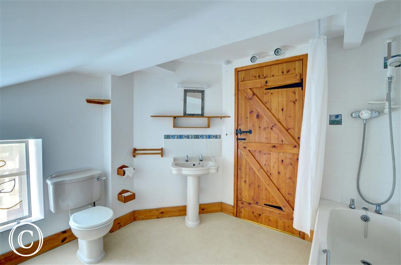 The main bathroom is spacious, with white suite and shower over the bath