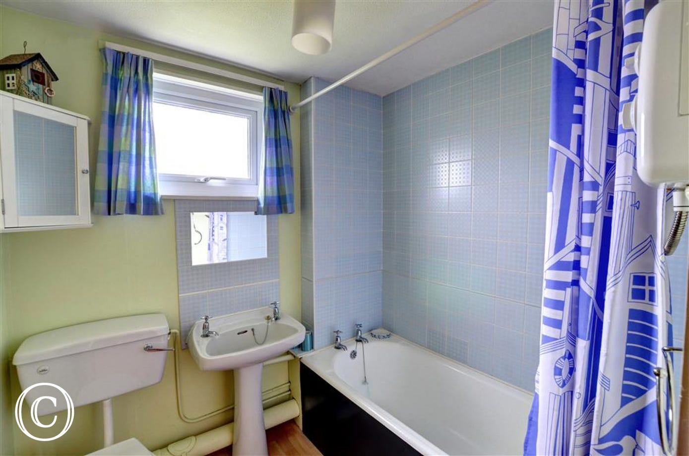 The bathroom, in shades of pastel blue and yellow, has an electric shower over the bath