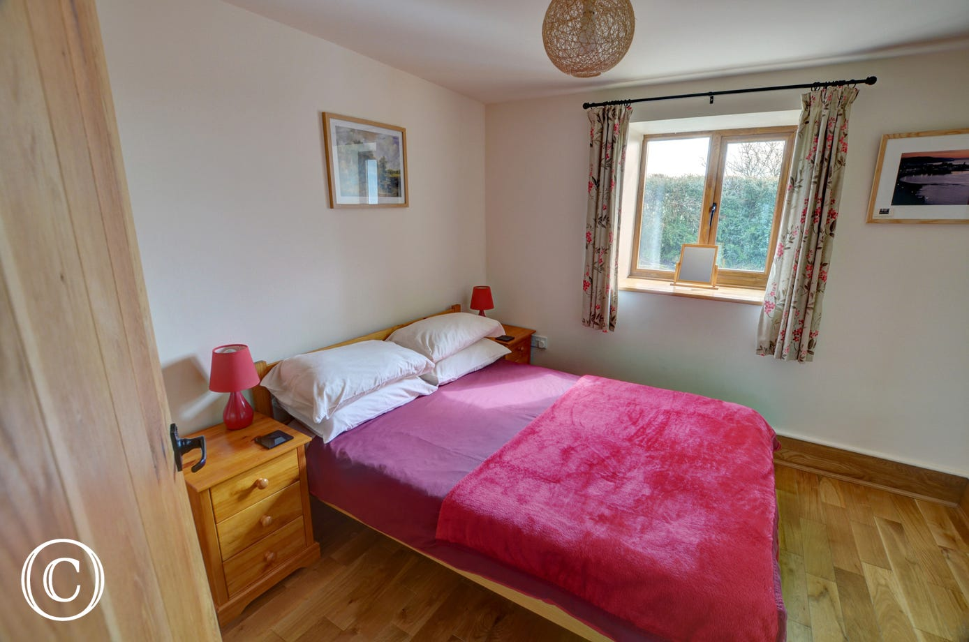 The double bedroom has a wooden bedstead and attractive furnishings