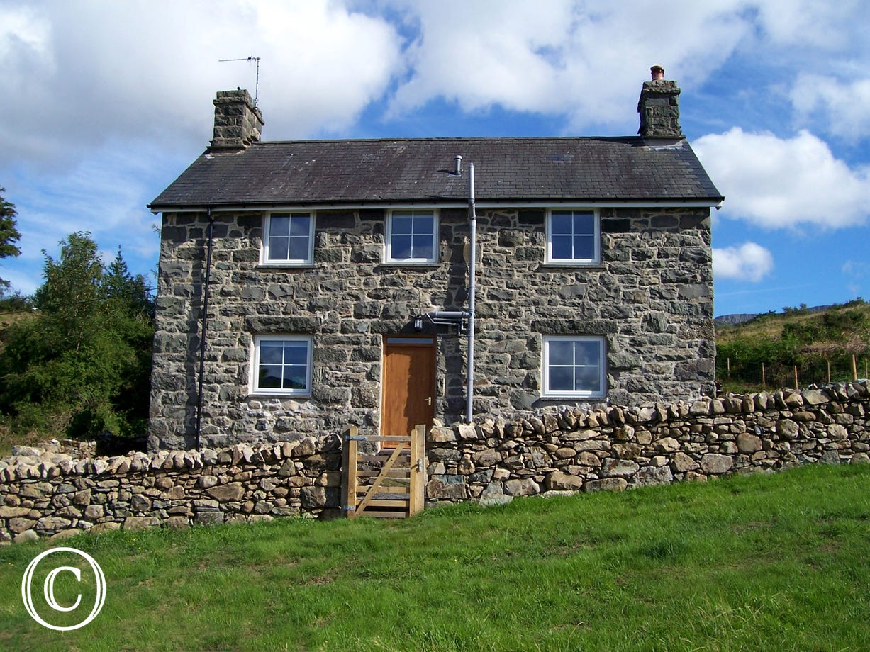 This lovely stone former farmhouse stands in a secluded location on the slopes below Cadair Idris