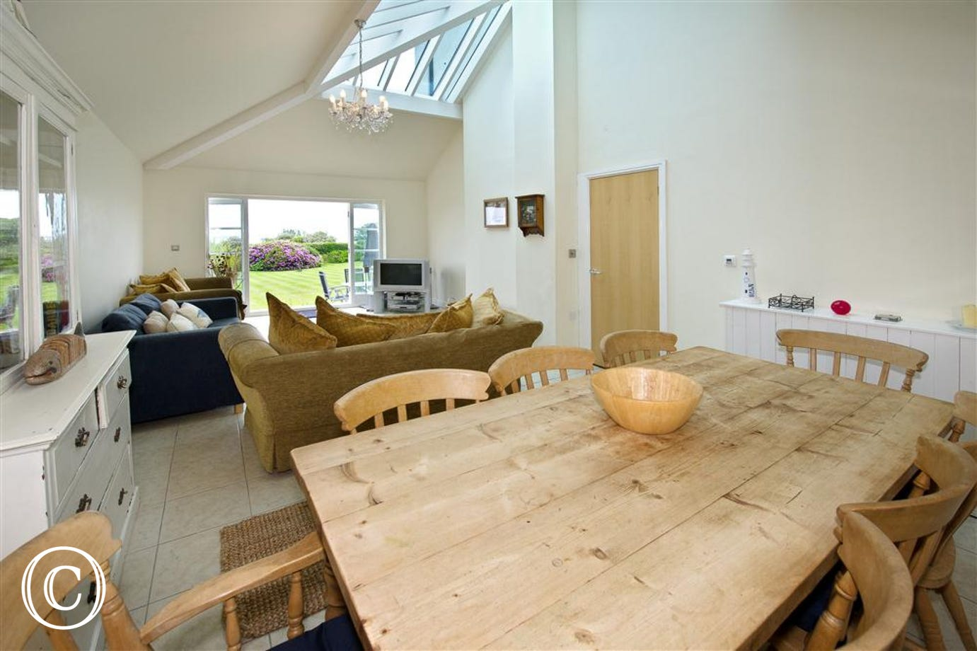 Conservatory to the rear of the property with sofa, double sofabed, and dining table & chairs