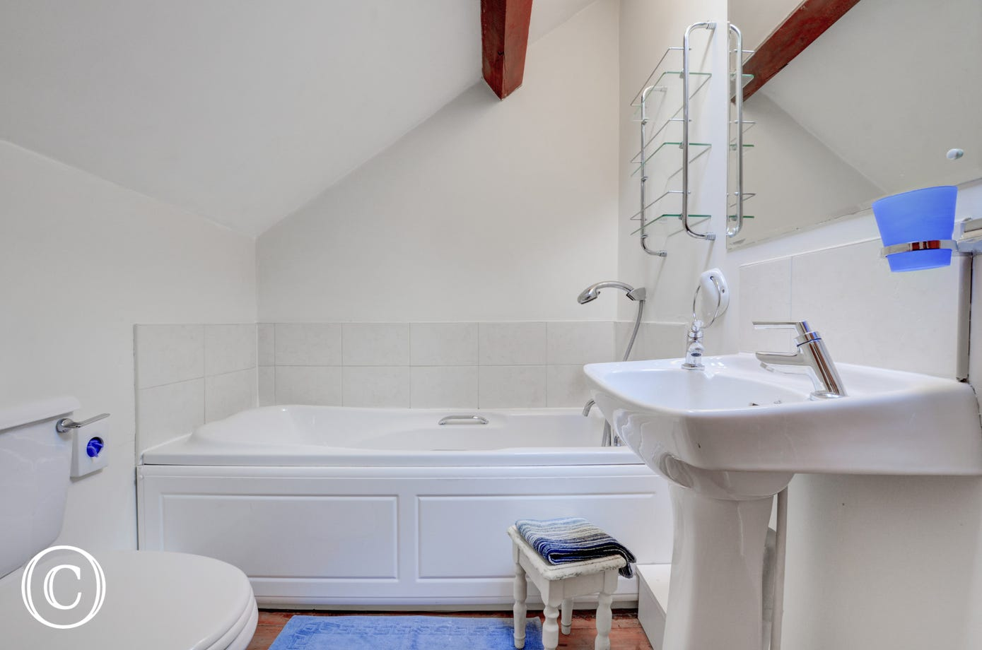 The bathroom has a white suite, with shower attachment over the bath