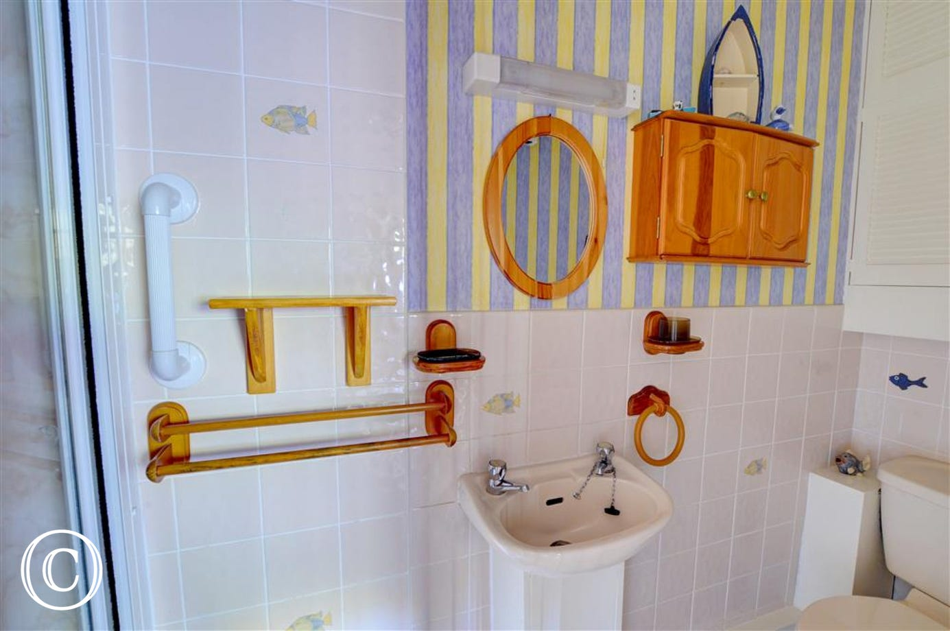 The en suite shower room has shower cubicle ( steps up), white WC and basin, and bright decor