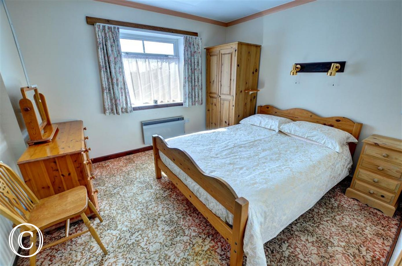 The double bedroom is furnished with a pine suite