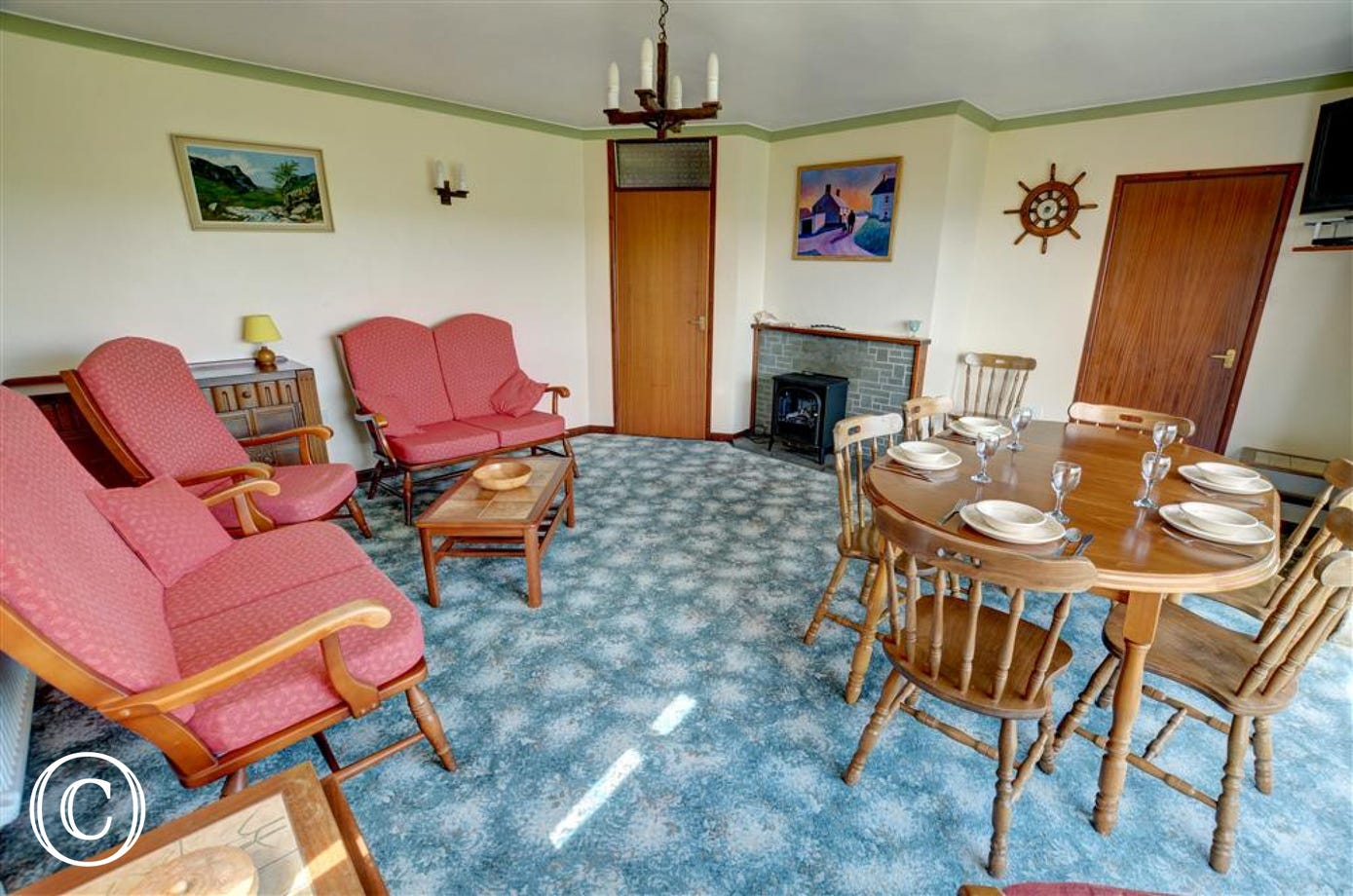 The living room has a cottage suite, dining table and chairs