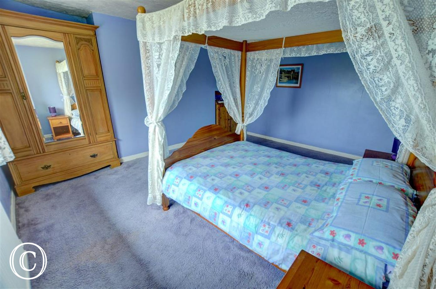 The master bedroom has a four-poster double bed and pine furniture