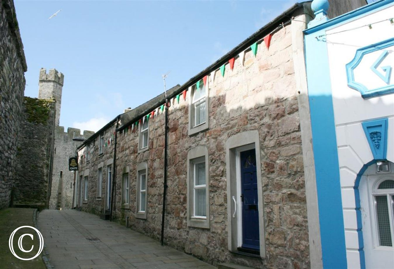 This mid-terraced stone cottage in Caernarfon is situated just inside the castle walls (to left of photo), in a pedestrianised street of cafes, bars and restaurants
