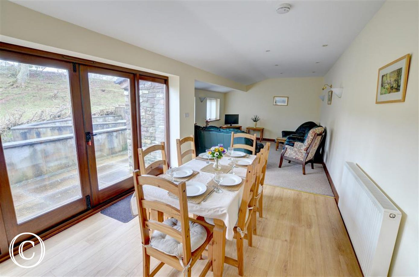 The spacious open plan living room has a dining table and chairs looking out through patio doors to the rear patio and surrounding countryside