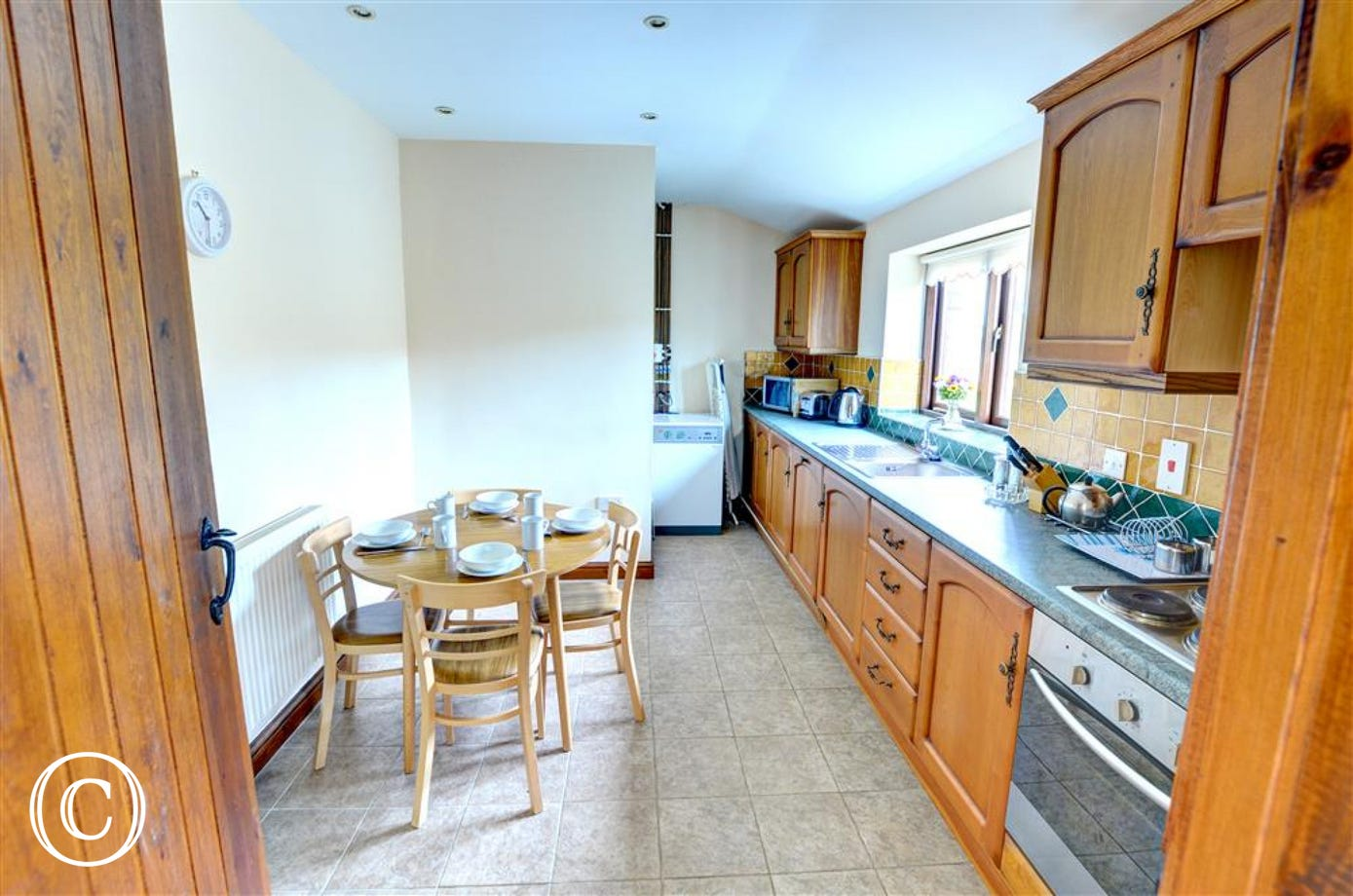The spacious kitchen includes a circular breakfast table and chairs