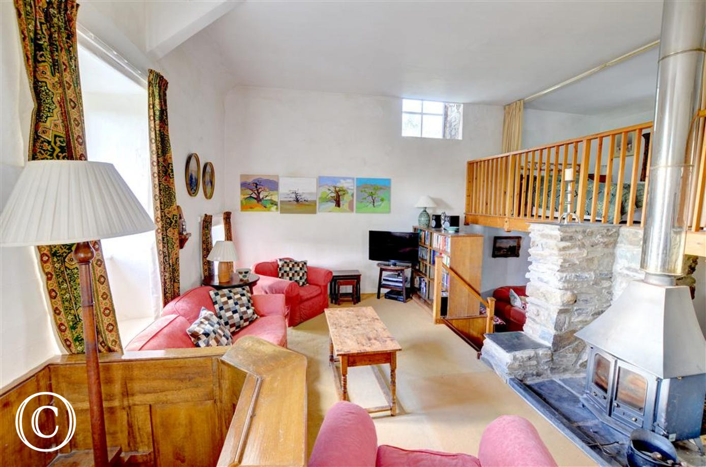 The open plan living accommodation is divided into distinct areas; the original pulpit and a woodburning stove are features of the sitting room