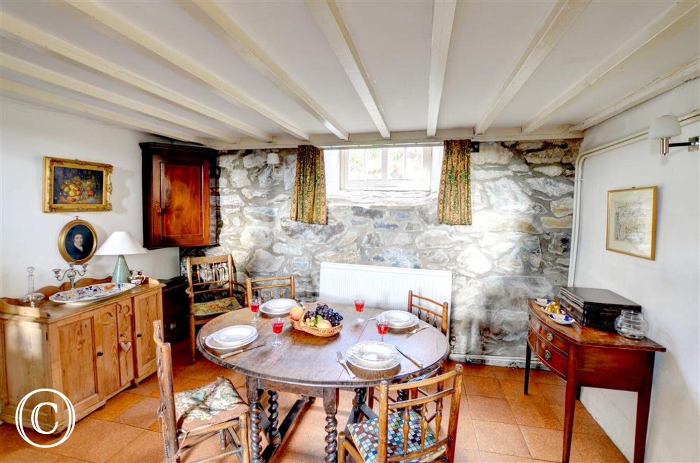The dinign room has exposed stone wall, antique furniture, crockery and cutlery