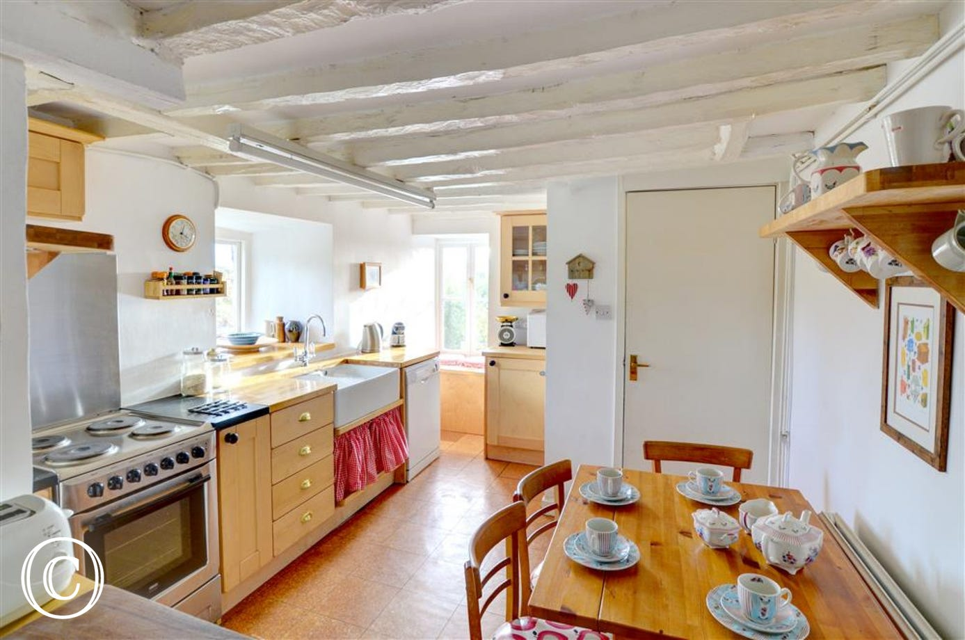 The bright kitchen has a Belfast sink and other traditional features, and includes a breakfast table and chairs for informal meals