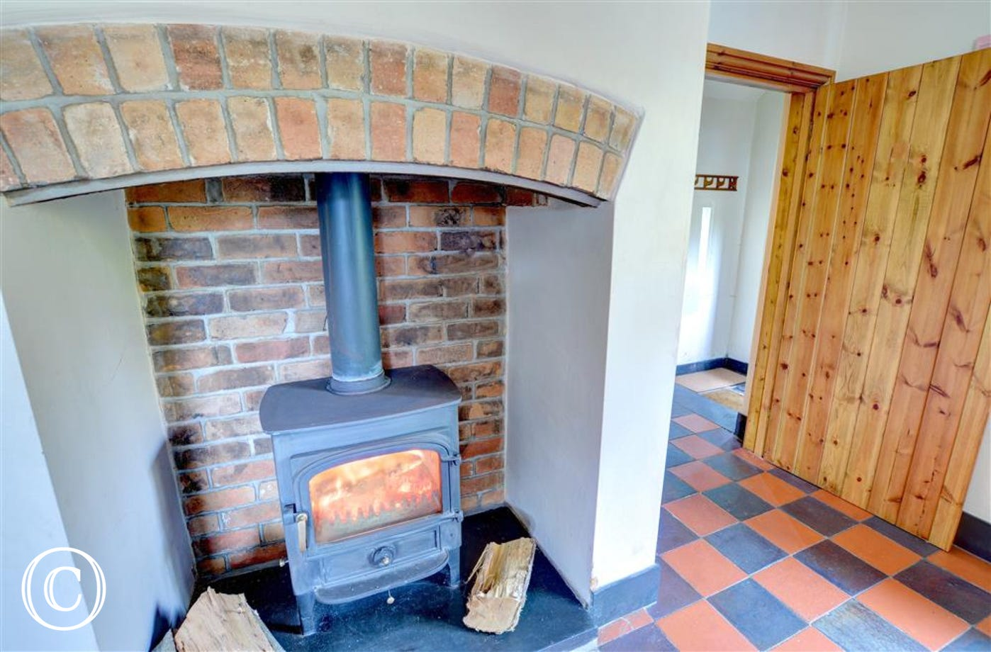 The kitchen's attractive brick fireplace has a woodburning stove