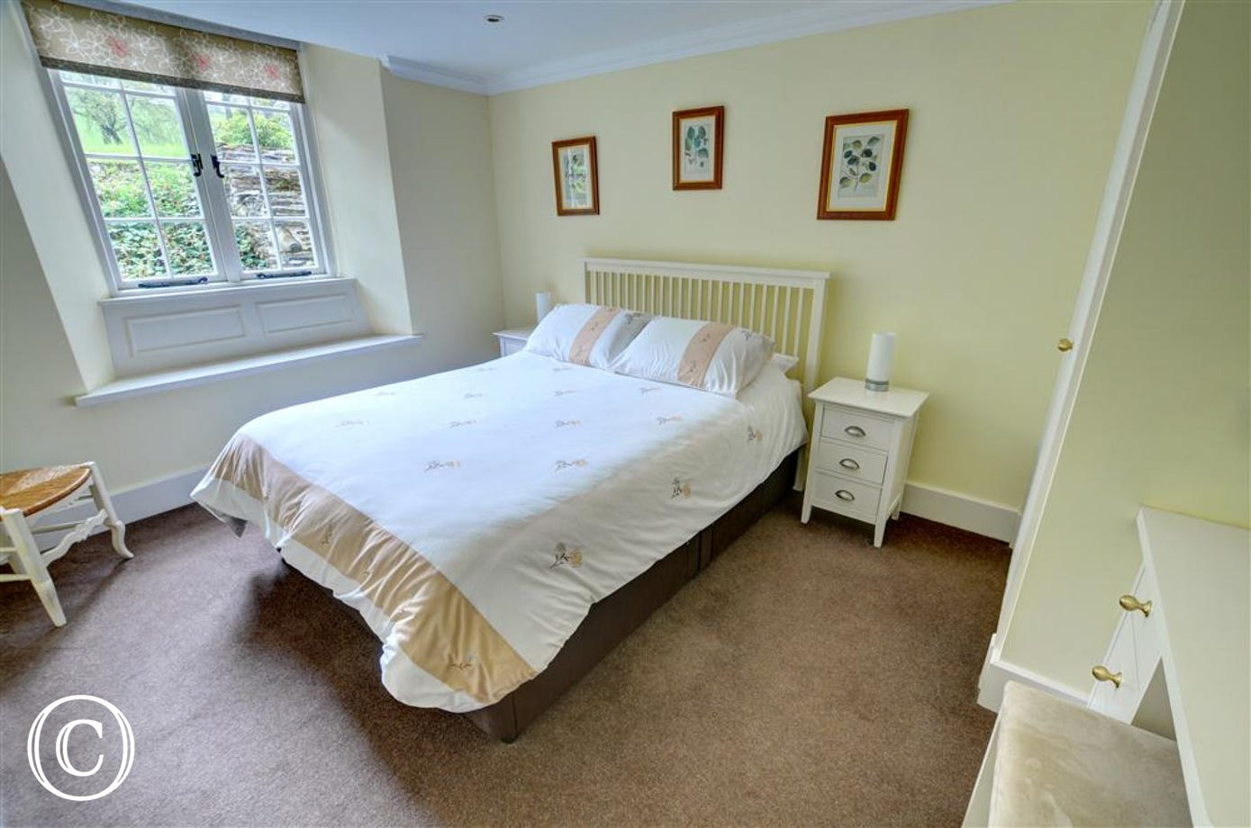The lovely light double bedroom has crisp white bed linen and a fresh neutral colour scheme