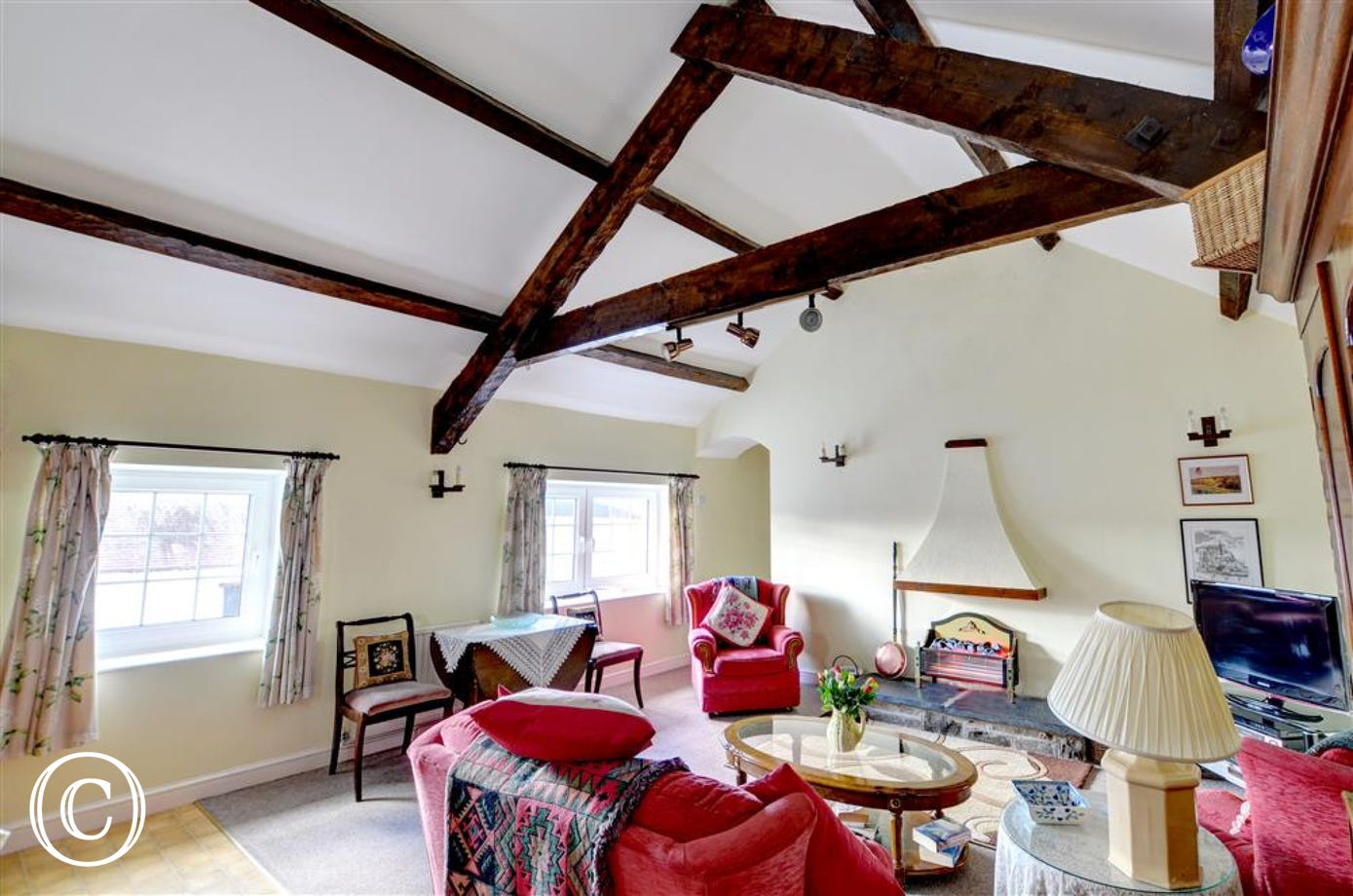 The sitting room is bright and airy with high ceilings and comfortable seating