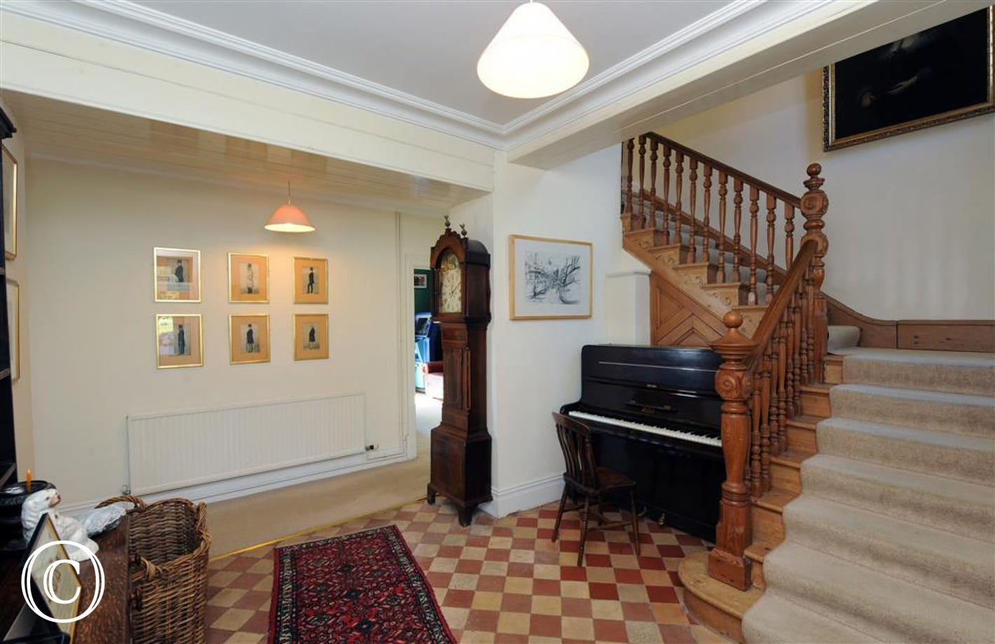 Enter into the welcoming hall with impressive pine staircase.