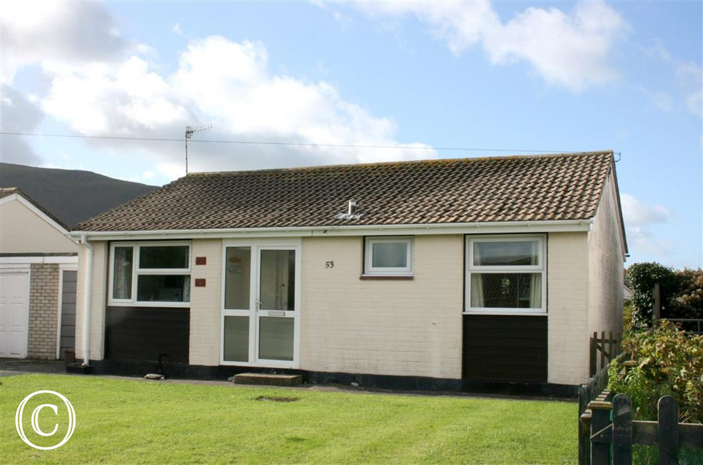 This neat bungalow in Fairbourne has a lawned garden to the front and parking on the driveway