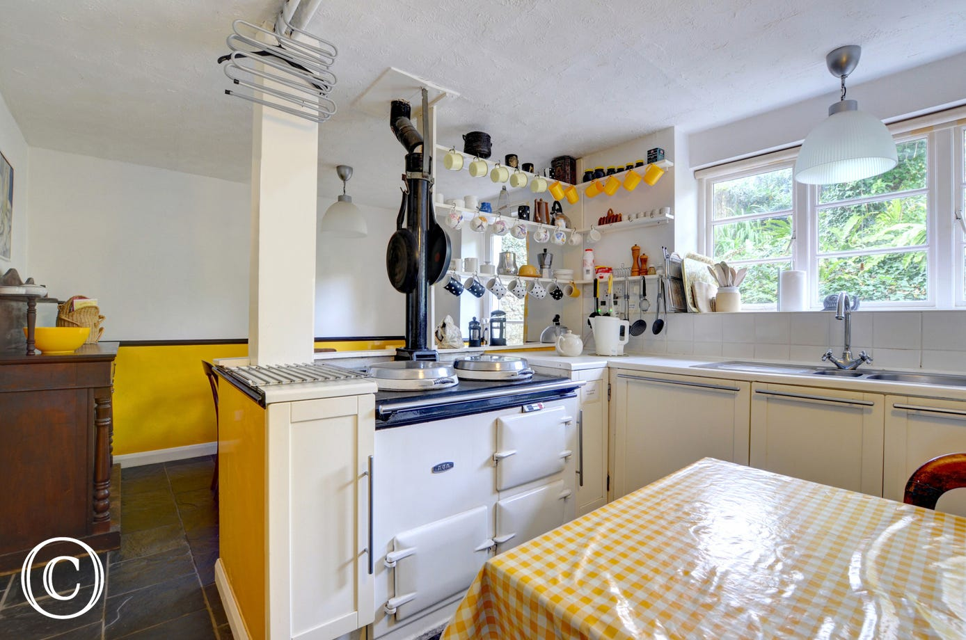 Quirky looking fitted kitchen/diner with oil-fired Aga and fridge/freeze
