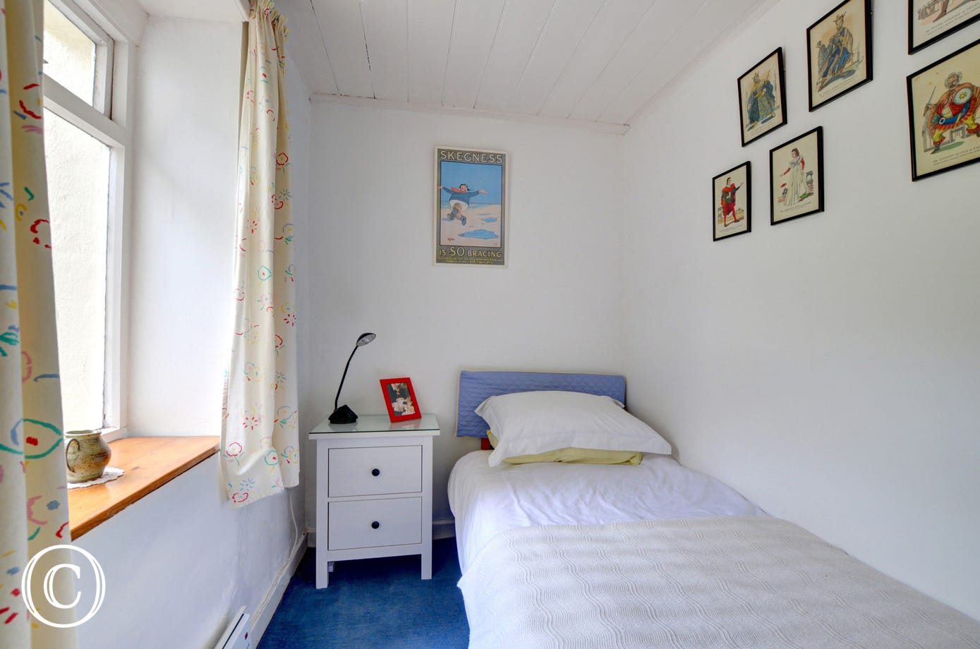 Tidy sized single bedroom with bedside cabinet and a chair