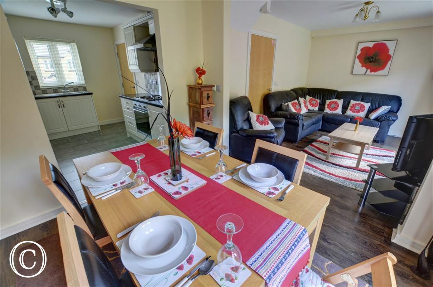 Comfortable leather seating at one end and dining table at the other, leading through to the kitchen