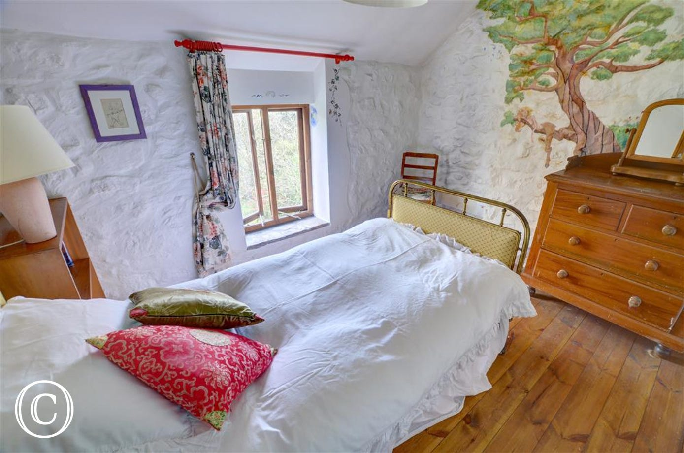Murals adorn the walls of this single bedroom, with emulsioned stone walls and pine floor