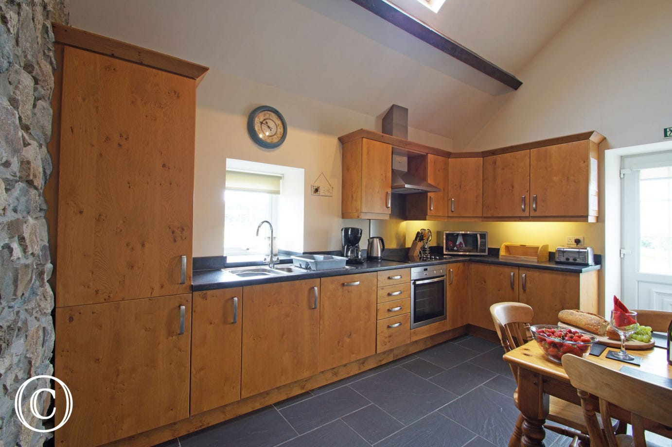 A character oak kitchen with slate floor and a farmhouse pine table