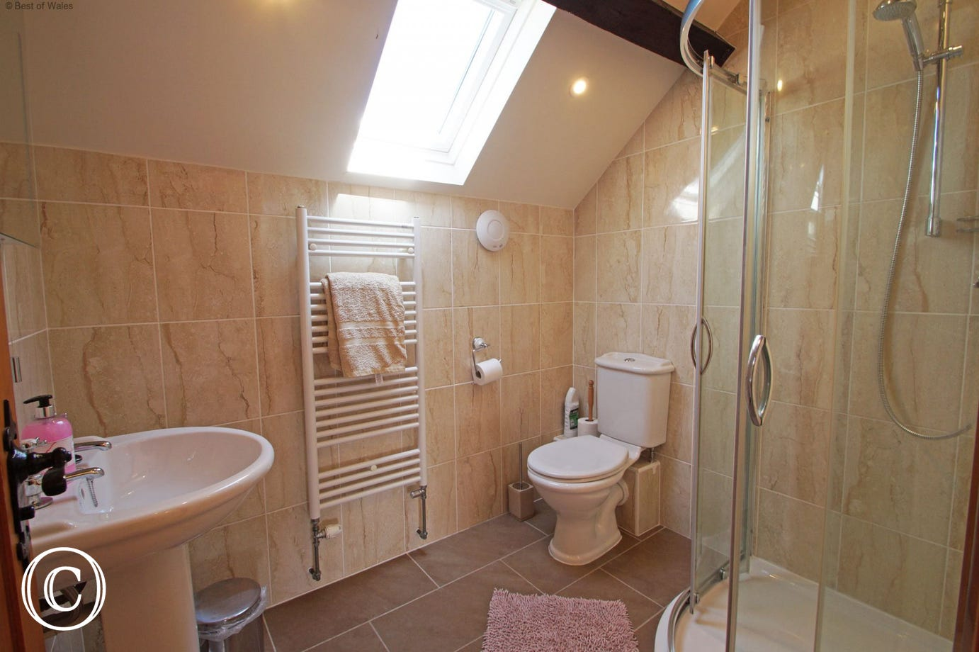 Fully tiled upstairs shower room with heated towel rail, WC and basin.