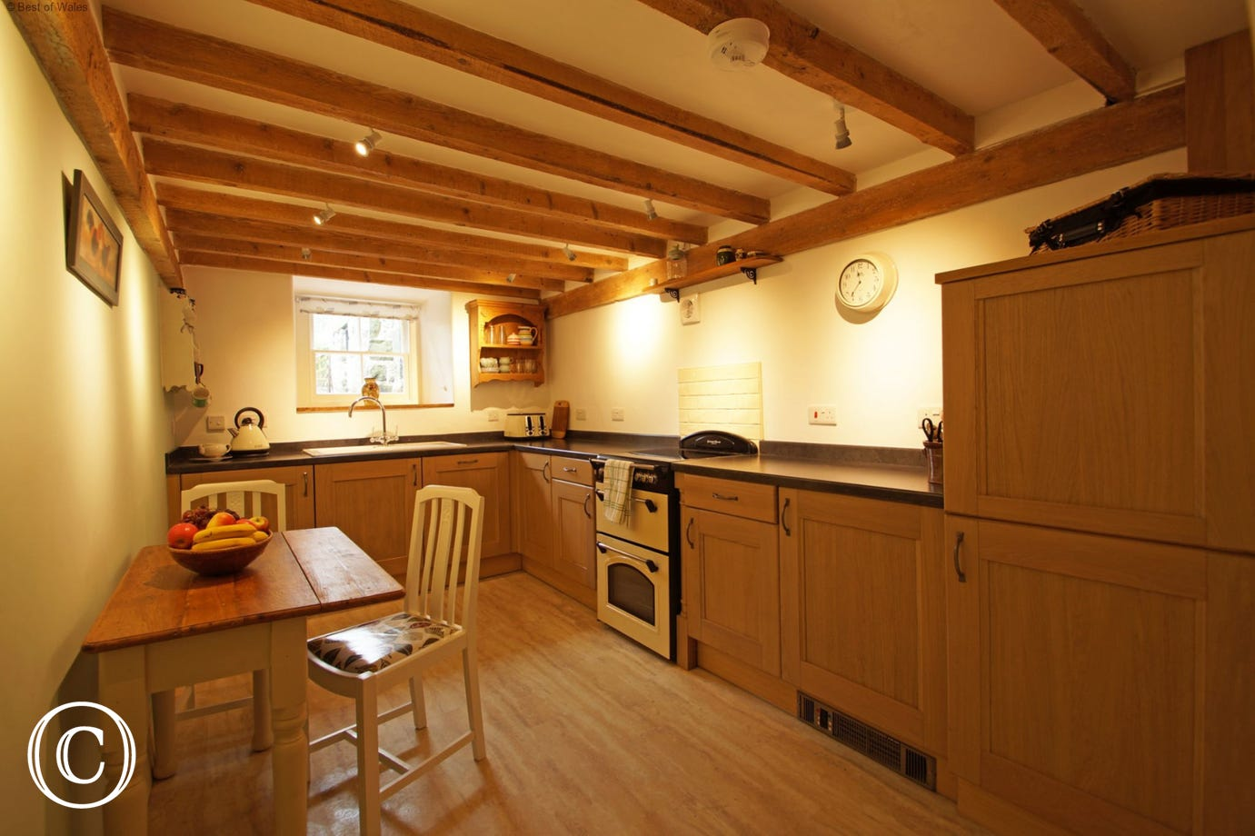 Fully equipped kitchen along with a small table and seating