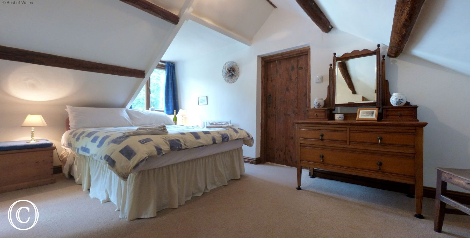 Spacious double bedroom with dressing table and countryside views