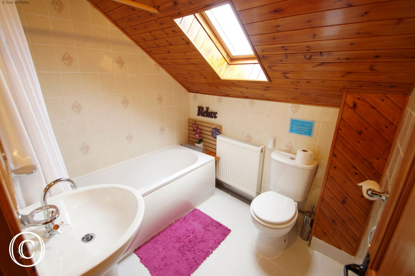 Bathroom includes bath with shower, WC and hand wash basin