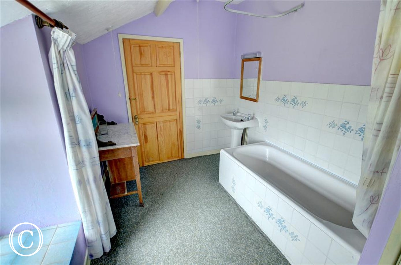 The upstairs family bathroom has WC and bath with an electric shower over
