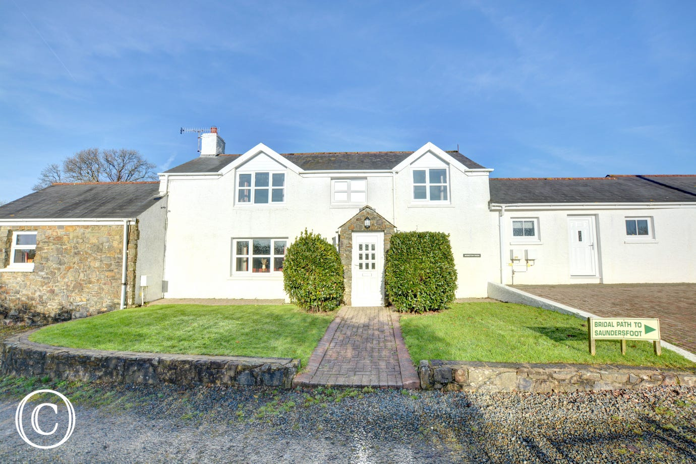 Exterior of Moreton Farmhouse with lawn to the front of the property, parking for 3 cars.