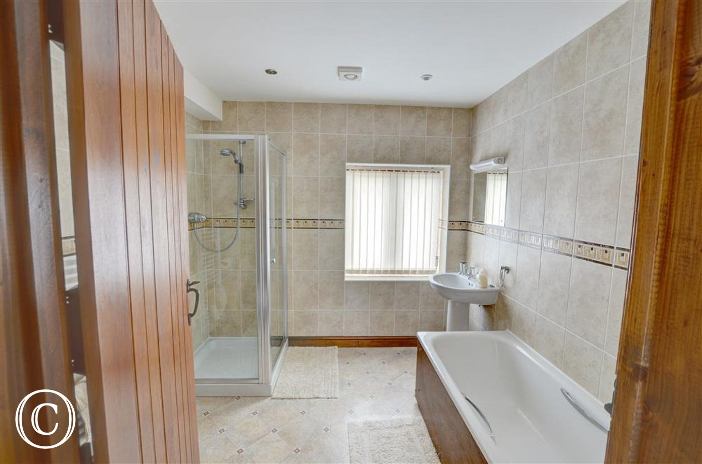 The bathroom is fully tiled, with a bath and separate shower cubicle