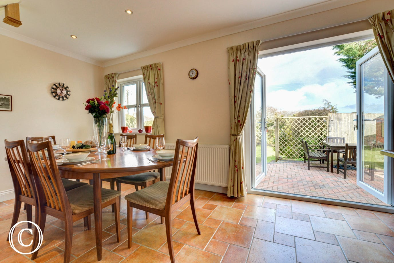 A dining table and chairs with patio door leading out onto a well presented garden